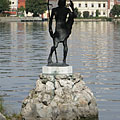 Statue of Saint John the Baptist in lake on a rock, behind the sculpture on the lakeshore the Hamary House can be seen - Tata, Hongrie