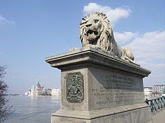 """One of the stone lion sculptures of Chain Bridge (Lánchíd) at the Buda-side abutment, the building of the Hungarian Parliament (Országház) is """"floating"""" over Danube in the distance - Budapest, Ungarn"""