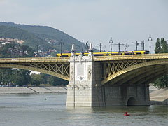 The middle pier of the Margaret Bridge at the Margaret Island, as well as a yellow Combino tram passes through the bridge - Budapest, Ungarn