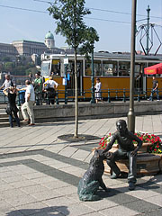 """""""Girl with a dog"""" bronze statue near the tram stop (and the Buda Castle in the background) - Budapest, Ungarn"""