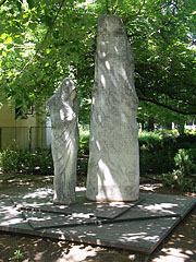 Statue of a mourning female figure who shut herself up, it is a World War II memorial under the trees - Siófok, Ungarn