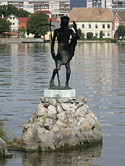Statue of Saint John the Baptist in lake on a rock, behind the sculpture on the lakeshore the Hamary House can be seen - Tata (Totis), Ungarn
