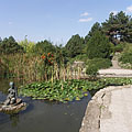 Fishpond in the Japanese Garden, and the statue of a seated female figure in the middle of it - Budapest, Ungarn