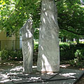 Statue of a mourning female figure who shut herself up, it is a World War II memorial under the trees - Siófok, Hongarije