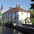 Lake Malom and the former watermill on its shore, and slightly further it is the steeple of the Roman Catholic church - Tapolca, Hongarije