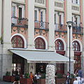 The Tiramisu Café on the ground floor of the former Hotel Mátra, next to it there's a fountain with a grapevine sculpture - Gyöngyös, Ungarn