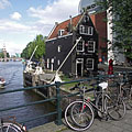 The small tilted house of the Café de Sluyswacht pub at the Oudeschans canal - Amsterdam, Netherlands