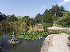 Fishpond in the Japanese Garden, and the statue of a seated female figure in the middle of it - Budapest, Hungary