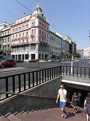 The stairs of the pedestrian underpass at the tram stop on the Small Boulevard, and the pink Grünbaum-Weiner apartment building in the background - Budapest, Hungary