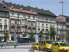Four-story residental buildings and yellow taxies in the north side of the Baross Square - Budapest, Hungary