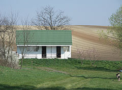 House on the lakeshore and plough fields behind it - Csővár, Hungary