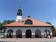 The building of the bus terminus, as well as the white steeple (tower) of the Reformed church - Nagykőrös, Hungary