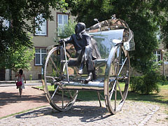 """Home-coming"", stainless steel statue at the theater in the park, representing Gyula Krúdy Hungarian writer who was born in Nyíregyháza, sitting on a two-wheeled coach - Nyíregyháza, Hungary"