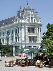 """Restaurant terrace in the town square, as well as the """"Takarékpalota"""" (""""Savings Bank's Palace"""") in the background - Nyíregyháza, Hungary"""