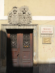 The door of the County Library was built in the late 18th century, above there are some carved crests - Pécs, Hungary