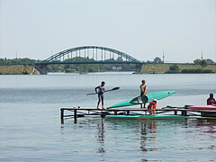 Kids on a pier preparing to go kayaking, and the Árpád Bridge can be seen behind them - Ráckeve, Hungary