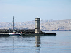 Another lighthouse on the cost at the harbor, with an island in the background - Senj, Croatia