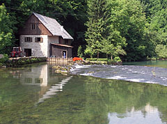 A stone house with a wooden water mill building on its side by the Slunjčica River (also known by the locals as Slušnica), opposite the hill with the castle ruins - Slunj, Croatia