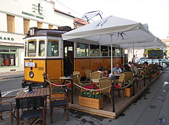 "The terrace of the ""Blues Café & 7-es megálló"" restaurant, including a yellow old tram - Szeged, Hungary"