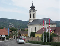 Streetscape with the Saint John the Baptist Roman Catholic Church, the hill with the houses of Nagymaros is over River Danube - Visegrád, Hungary